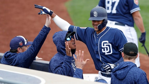 San Diego Padres shortstop Fernando Tatis, right, celebrates with teammates after hitting a home run during the eighth inning of a spring training baseball game against the Seattle Mariners, Friday, Feb. 23, 2018, in Peoria, Ariz. (AP Photo/Charlie Neibergall)