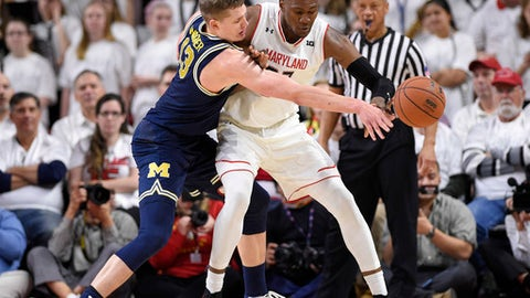 Michigan forward Moritz Wagner, left, reaches for the ball against Maryland forward Bruno Fernando, right, during the first half of an NCAA college basketball game, Saturday, Feb. 24, 2018, in College Park, Md. Wagner was called for a foul on the play. (AP Photo/Nick Wass)