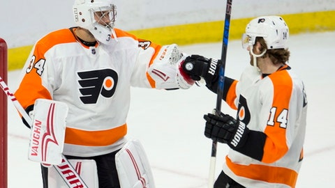 Philadelphia Flyers goaltender Petr Mrazek, left, and center Sean Couturier celebrate after defeating the Ottawa Senators 5-3 in NHL action, Saturday, Feb. 24, 2018 in Ottawa. (Adrian Wyld/The Canadian Press via AP)