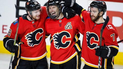 Calgary Flames' Troy Brouwer, center, celebrates his goal with teammates Matt Stajan, left, and T.J. Brodie during third-period NHL hockey game action against the Colorado Avalanche in Calgary, Alberta, Saturday, Feb. 24, 2018. (Jeff McIntosh/The Canadian Press via AP)