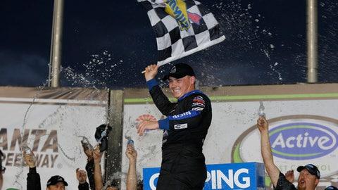 Brett Moffitt waves a checkered flag after winning the NSCAR Truck Series auto race at Atlanta Motor Speedway in Hampton, Ga., Saturday, Feb. 24, 2018. (AP Photo/John Bazemore)