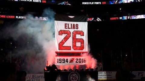 The jersey of Patrik Elias, of the Czech Republic, is raised to the ceiling as the New Jersey Devils retire his number before an NHL hockey game against the New York Islanders Saturday, Feb. 24, 2018, in Newark, N.J. (AP Photo/Bill Kostroun)