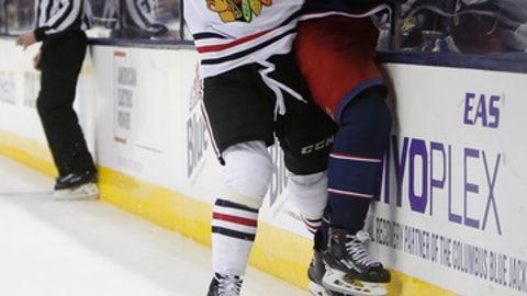 Chicago Blackhawks' Erik Gustafsson, left, of Sweden, checks Columbus Blue Jackets' Josh Anderson during the second period of an NHL hockey game Saturday, Feb. 24, 2018, in Columbus, Ohio. (AP Photo/Jay LaPrete)