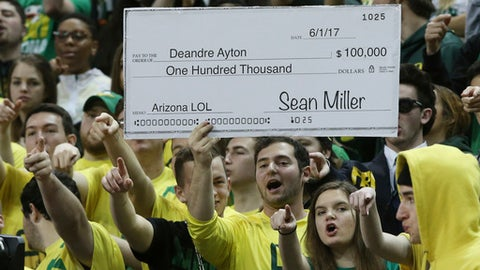 Fans in the Oregon student section hold up a sign making fun of the controversy surrounding Arizona coach Sean Miller, during the first half of an NCAA college basketball game Saturday, Feb. 24, 2018, in Eugene, Ore. (AP photo/Chris Pietsch)