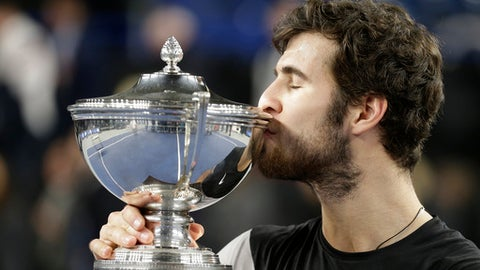 Karen Khachanov of Russia kisses his trophy after defeating Lucas Pouille of France during their final match at the Open 13 Provence tennis tournament in Marseille, southern France, Sunday Feb.25, 2018.(AP Photo/Claude Paris)