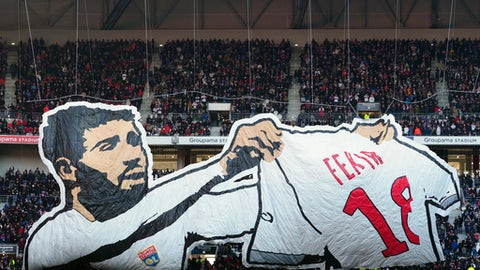 Lyon supporters wave a flag depicting Lyon's player Nabil Fekir during their French League One soccer match against Saint-Etienne, in Decines, near Lyon, central France, Sunday, Feb. 25, 2018. (AP Photo/Laurent Cipriani)