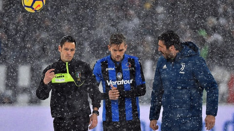From left, referee Maurizio Mariani, Atalanta's Rafael Toloi and Juventus goalie Gianluigi Buffon walk on the pitch of the Allianz Stadium in Turin, Italy, Sunday, Feb. 25, 2018. Snowfall has prompted the Serie A match between six-time defending champion Juventus and Atalanta to be postponed. Fans filled the Allianz Stadium shortly before the scheduled kickoff Sunday but when the referee could not roll the ball on the snow-covered pitch, the game was quickly called off. (Alessandro Di Marco/ANSA via AP)
