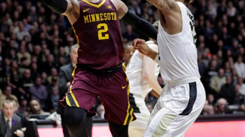 Minnesota guard Nate Mason, left, shoots over Purdue forward Vincent Edwards, right,  in the first half of an NCAA college basketball game in West Lafayette, Ind., Sunday, Feb. 25, 2018. (AP Photo/Michael Conroy)