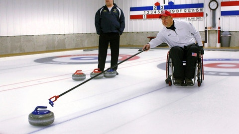 Former Connecticut basketball player Steve Emt practices his curling at the Norfolk Curling Club in Norfolk, Conn., Wednesday, Feb. 21, 2018. Emt, who was paralyzed in a drunk driving accident in 1995, is the vice skip on the U.S. team that will participate in next month's Paralympic Games in South Korea. At rear is Ray Robitaille, of the Norfolk Curling Club. (AP Photo/Pat Eaton-Robb)