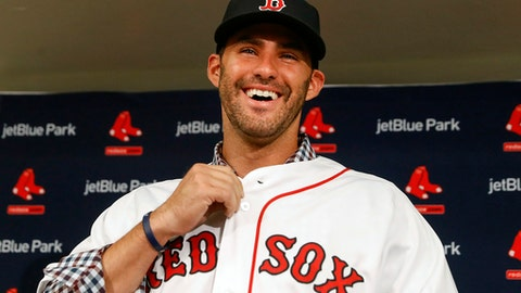 Boston Red Sox baseball player J.D. Martinez smiles as he buttons up his jersey during an introductory news conference, Monday, Feb. 26, 2018, in Fort Myers, Fla. (AP Photo/John Minchillo)