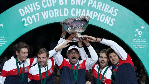 FILE - This is a Sunday, Nov. 26, 2017  file photo of  the French captain Yannick Noah, center, holding the cup after France won the Davis Cup at the Pierre Mauroy stadium in Lille, northern France.  France won the Davis Cup for the first time in 16 years after beating Belgium 3-2. The Davis Cup is set to be transformed into a one-week, 18-nation World Cup of Tennis in a major overhaul of the international team event in mens tennis. The International Tennis Federation says it has unanimously endorsed a proposal to create a new season-ending event in November starting in 2019. The World Cup of Tennis would be played over seven days in the traditional week of the David Cup final and comprise a round-robin format followed by a quarterfinal knockout stage. (AP Photo/Christophe Ena)