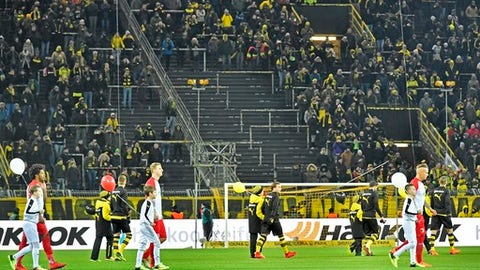 Players enter the pitch in front of empty places on the famous Dortmund South Tribune for the German Bundesliga soccer match between Borussia Dortmund and FC Augsburg in Dortmund, Germany, Monday, Feb 26, 2018. Thousands of supporters protest against Bundesliga matches on Mondays. (AP Photo/Martin Meissner)