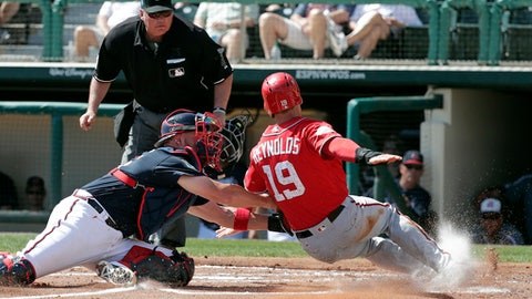 Atlanta Braves catcher Tyler Flowers, left, tags out Washington Nationals' Matt Reynolds as he tagged up on fly ball in the second inning of an exhibition spring baseball game, Monday, Feb. 26, 2018, in Kissimmee, Fla. (AP Photo/John Raoux)