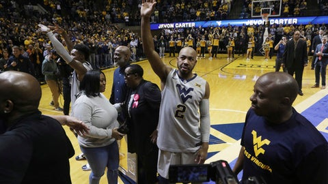 West Virginia guard Jevon Carter (2) waves to the crowd on Senior night before the start of an NCAA college basketball game against Texas Tech Monday, Feb. 26, 2018, in Morgantown, W.Va. (AP Photo/Raymond Thompson)