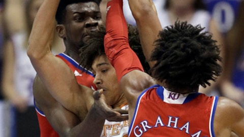 Texas forward Jericho Sims (20) tries to split Kansas defenders Udoka Azubuike, back, and Devonte' Graham (4) during the first half of an NCAA college basketball game in Lawrence, Kan., Monday, Feb. 26, 2018. (AP Photo/Orlin Wagner)