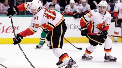 Calgary Flames left wing Matthew Tkachuk (19) shoots as center Sean Monahan (23) watches in the second period of the team's NHL hockey game against the Dallas Stars on Tuesday, Feb. 27, 2018, in Dallas. (AP Photo/Tony Gutierrez)