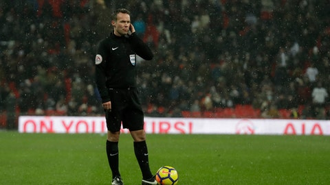 Referee Paul Tierney gets advice on the radio from the VAR system during the English FA Cup fifth round replay soccer match between Tottenham Hotspur and Rochdale at Wembley stadium in London, Wednesday, Feb. 28, 2018. (AP Photo/Matt Dunham)