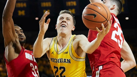 Feb 18, 2018; Ann Arbor, MI, USA; Michigan Wolverines guard Duncan Robinson (22) shoots against Ohio State Buckeyes forward Keita Bates-Diop (33) and forward Kyle Young (25) in the first half at Crisler Center. Mandatory Credit: Rick Osentoski-USA TODAY Sports