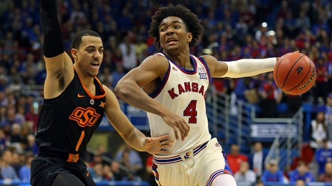 Feb 3, 2018; Lawrence, KS, USA; Kansas Jayhawks guard Devonte' Graham (4) dribbles the ball as Oklahoma State Cowboys guard Kendall Smith (1) defends in the second half at Allen Fieldhouse. Mandatory Credit: Jay Biggerstaff-USA TODAY Sports