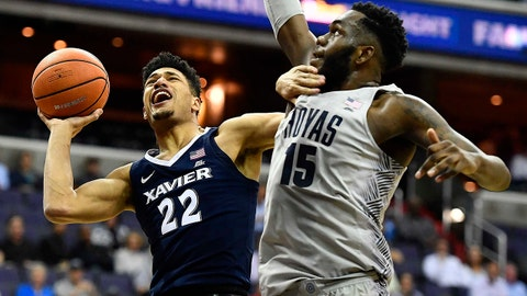 Feb 21, 2018; Washington, DC, USA; Xavier Musketeers forward Kaiser Gates (22) scores a layup as Georgetown Hoyas center Jessie Govan (15) defends during the first half at Capital One Arena. Mandatory Credit: Brad Mills-USA TODAY Sports