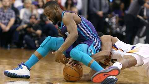 CORRECTS TO SUNDAY NOT SATURDAY - Charlotte Hornets guard Kemba Walker, left, and Phoenix Suns' T.J. Warren battle for the ball during the first half of an NBA basketball game Sunday, Feb. 4, 2018, in Phoenix. (AP Photo/Ralph Freso)