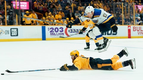St. Louis Blues left wing Jaden Schwartz (17) leaps over a fallen Nashville Predators defenseman Ryan Ellis (4) as he tries to play the puck in the third period of an NHL hockey game Tuesday, Feb. 13, 2018, in Nashville, Tenn. (AP Photo/Sanford Myers