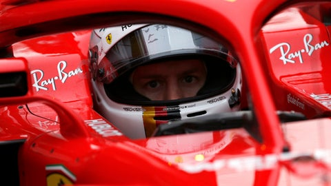 Ferrari driver Sebastian Vettel of Germany sits in his car cockpit in the pit lane during a Formula One pre-season testing session at the Catalunya racetrack in Montmelo, outside Barcelona, Spain, Tuesday, Feb. 27, 2018. (AP Photo/Francisco Seco)
