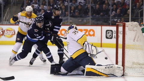 Winnipeg Jets' Mark Scheifele (55) scores on Nashville Predators goaltender Pekka Rinne (35) as he's checked by Mattias Ekholm (14), while Jets' Kyle Connor (81) watches during the second period of an NHL hockey game Tuesday, Feb. 27, 2018, in Winnipeg, Manitoba. (Trevor Hagan/The Canadian Press via AP)