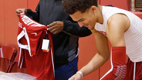 FILE - In this Feb. 2, 2018, file photo, Oklahoma guard Trae Young autographs jerseys under the watchful eye of his father, Rayford Young, in Norman, Okla. His decision to attend Oklahoma has given him an irreplaceable experience with his father, former Texas Tech guard Rayford Young. (AP Photo/Sue Ogrocki, File)