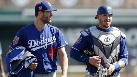 Los Angeles Dodgers starting pitcher Clayton Kershaw (22) walks out with catcher Yasmani Grandal before a spring training baseball game against the Chicago White Sox, Friday, March 2, 2018, in Glendale, Ariz. (AP Photo/Carlos Osorio)
