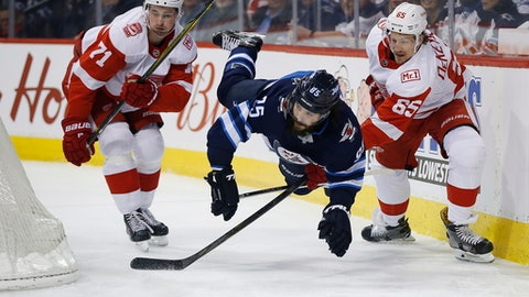 Winnipeg Jets' Mathieu Perreault (85) is tripped by Detroit Red Wings' Danny DeKeyser (65) as Dylan Larkin (71) looks for the puck during the second period of an NHL hockey game Friday, March 2, 2018, in Winnipeg, Manitoba. (John Woods/The Canadian Press via AP)