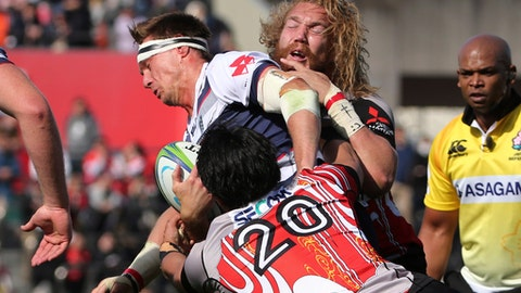 Dane Haylett Petty of Australia's Rebels is tackled by Yoshitaka Tokunaga (20) and Willem Britz of Japan's Sunwolves during their Super Rugby match in Tokyo, Saturday, March 3, 2018. (AP Photo/Koji Sasahara)