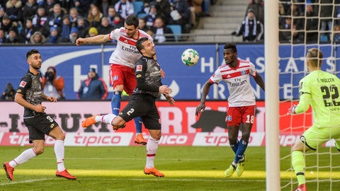 Mainz'  Gerrit Holtmann, left, Hamburg's Filip Kostic, second left, Mainz' Giulio Donati, center, Hamburg's Bakery Jatta, second right, and Mainz' goalie Florian Mueller, right, challenge for the ball  during the German Bundesliga soccer match between Hamburger SV and FSV Mainz 05, in Hamburg, Germany, Saturday, March 3, 2018.  (Axel Heimken/dpa via AP)