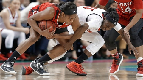 North Carolina State's Kiara Leslie, left, holds onto the ball as Louisville's Jazmine Jones, right, defends during the first half of a Women's Atlantic Coast Conference basketball tournament semifinal game in Greensboro, N.C., Saturday, March 3, 2018. (AP Photo/Chuck Burton)