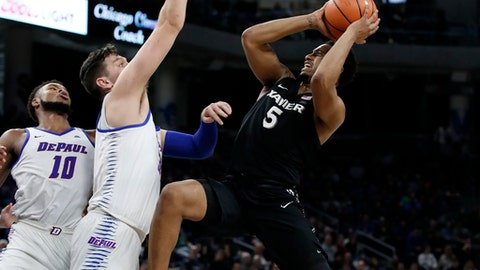 Xavier guard Trevon Bluiett (5) shoots against DePaul center Marin Maric, center, and DePaul forward Tre'Darius McCallum (10) during the second half of an NCAA college basketball game Saturday, March 3, 2018, in Chicago, Ill. (AP Photo/Jim Young)