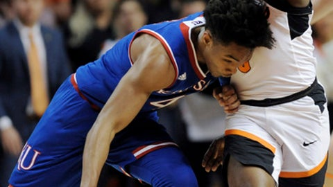 Kansas guard Devonte Graham, left, drives against Oklahoma State guard Brandon Averette during an NCAA college basketball game in Stillwater, Okla., Saturday, March. 3, 2018. (AP Photo/Brody Schmidt)