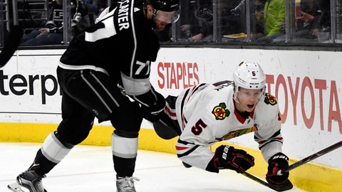 Chicago Blackhawks defenseman Connor Murphy (5) is knocked to the ice by Los Angeles Kings center Jeff Carter (77) during the second period of an NHL hockey game, Saturday, March 3, 2018, in Los Angeles. (AP Photo/Michael Owen Baker)
