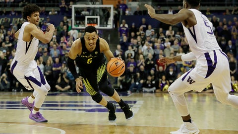 Oregon guard Elijah Brown drives between Washington guards Matisse Thybulle, left, and Jaylen Nowell, right, during the second half of an NCAA college basketball game, Saturday, March 3, 2018, in Seattle. Oregon won 72-64. (AP Photo/Ted S. Warren)