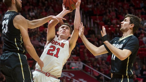 Utah forward Tyler Rawson (21) shoots between Colorado forward Lucas Siewert (23) and guard Lazar Nikolic (11) during an NCAA college basketball game in Salt Lake City on Saturday, March 3, 2018. (Rick Egan/The Salt Lake Tribune via AP)