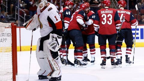 Ottawa Senators goaltender Mike Condon (1) pulls the puck from the net as Arizona Coyotes left wing Jordan Martinook (48) celebrates his goal with center Brad Richardson (15), center Nick Cousins (25), defenseman Alex Goligoski (33) and defenseman Niklas Hjalmarsson (4) during the second period of an NHL hockey game Saturday, March 3, 2018, in Glendale, Ariz. (AP Photo/Ross D. Franklin)