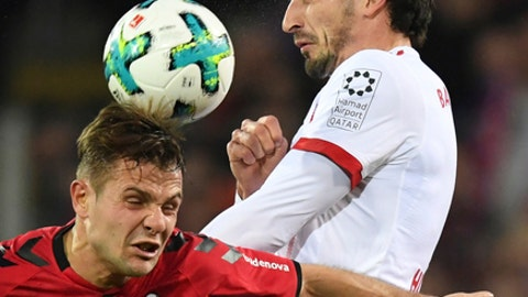 Freiburg's Amir Abrashi, left, challenges for the ball with Munich's Mats Hummels during the German Bundesliga soccer match between SC Freiburg and Bayern Munich, in Freiburg, Germany, Sunday, March 4, 2018. (Patrick Seeger/dpa via AP)