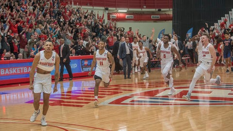 Radford guard Carlik Jones, left, celebrates after sinking a three-point basket to win as teammates Travis Fields Jr (11), Donald Hicks (5) and Caleb Tanner, right, also celebrate after the Big South Conference championship NCAA college basketball game against Liberty, Sunday, March 4, 2018, in Radford Va. (AP Photo/Don Petersen)