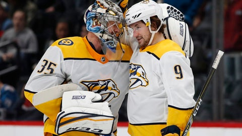 Nashville Predators goaltender Pekka Rinne, left, congratulates left wing Filip Forsberg who scored the winning goal against the Colorado Avalanche in overtime of an NHL hockey game Sunday, March 4, 2018, in Denver. (AP Photo/David Zalubowski)