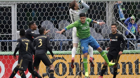 Seattle Sounders defender Tony Alfaro, second from right, collides with Los Angeles goalkeeper Tyler Miller (1) during the first half of an MLS soccer match, Sunday, March 4, 2018, in Seattle. (AP Photo/Ted S. Warren)