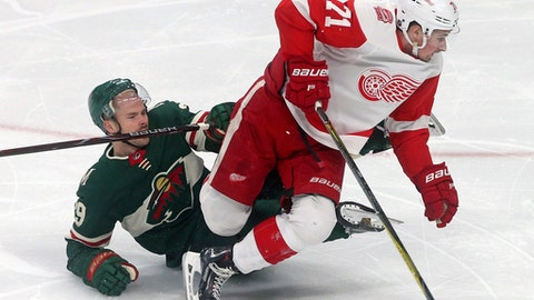 Detroit Red Wings' Dylan Larkin, right, leaves Minnesota Wild's Nate Prosser on the ice after a collision in the first period of an NHL hockey game Sunday, March 4, 2018, in St. Paul, Minn. (AP Photo/Jim Mone)