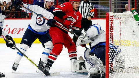 Carolina Hurricanes' Jeff Skinner (53) is pushed into Winnipeg Jets goaltender Connor Hellebuyck (37) by Jets' Dmitry Kulikov (5) during the second period of an NHL hockey game, Sunday, March 4, 2018, in Raleigh, N.C. (AP Photo/Karl B DeBlaker)