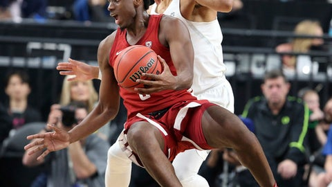 Washington State's Robert Franks, left, tries to pass as he falls to the court as Oregon's Elijah Brown defends during the first half of an NCAA college basketball game in the first round of the Pac-12 men's tournament Wednesday, March 7, 2018, in Las Vegas. (AP Photo/Isaac Brekken)