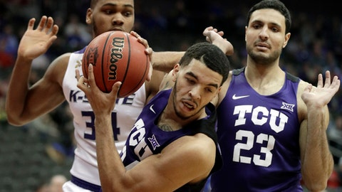 TCU guard Kenrich Williams, front, rebounds in front of Kansas State forward Levi Stockard III (34) and TCU forward Ahmed Hamdy-Mohamed (23) during the first half of an NCAA college basketball game in quarterfinals of the Big 12 conference tournament in Kansas City, Mo., Thursday, March 8, 2018. (AP Photo/Orlin Wagner)