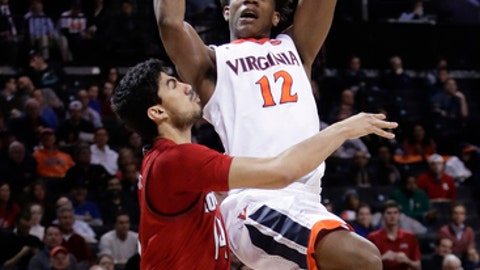 Virginia's De'Andre Hunter (12) shoots over Louisville's Anas Mahmoud (14) during the second half of an NCAA college basketball game in the quarterfinal round of the Atlantic Coast Conference tournament Thursday, March 8, 2018, in New York. Virginia won 75-58. (AP Photo/Frank Franklin II)