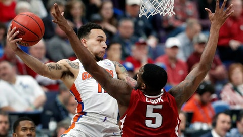 Florida's Chris Chiozza, left, passes under the basket around Arkansas' Arlando Cook (5) during the first half of an NCAA college basketball game in the quarterfinals of the Southeastern Conference tournament, Friday, March 9, 2018, in St. Louis. (AP Photo/Jeff Roberson)